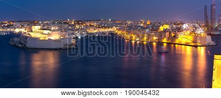 Panoramic aerial skyline view of ancient defences of Three cities, three fortified cities of Birgu, Senglea and Cospicua and Grand Harbor, as seen from Valletta at night, Malta.