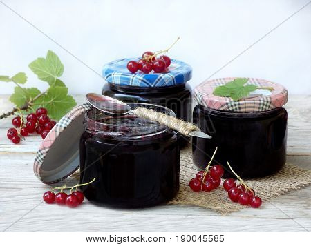 Three Jar Of Jam From The Red Currant On A Wooden Background. Berries Frayed With Sugar