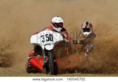 ALVELEY,UK - MAY 7: A sidecar team competing in the Bewdley MCC spring grasstrack meeting accelerate out of the top corner in a cloud of dust on May 7, 2017 in Alveley