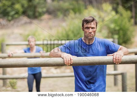 Tired man and woman leaning on a hurdle during obstacle course in boot camp