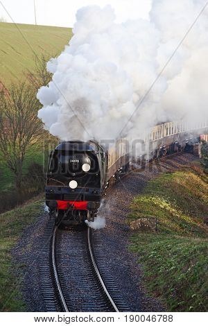 BICKNOLLER, UK - MARCH 27: A vintage steam train heads toward Minehead with a rake of passenger coaches full of paying customers during the WSR Spring steam gala on March 27, 2014 in Bicknoller
