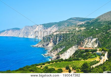Cephalonia shore cliffs and blue coastal sea waters. Olive plantage in foreground.