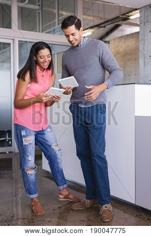 Smiling business colleagues looking at tablet computer while standing in office