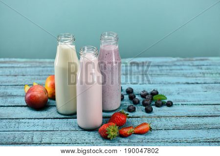 Homemade Fruity Milkshakes In Glass Bottles With Fresh Ingredients On Tabletop On Blue