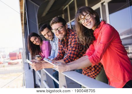 Portrait of smiling business colleagues leaning on railing at balcony