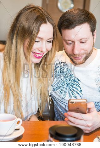 Closeup of couple listening to music with mobile phone at coffee bar. Man and woman listening music with headphones.