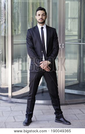 portrait of handsome man standing in a suit and tie in front of glass door
