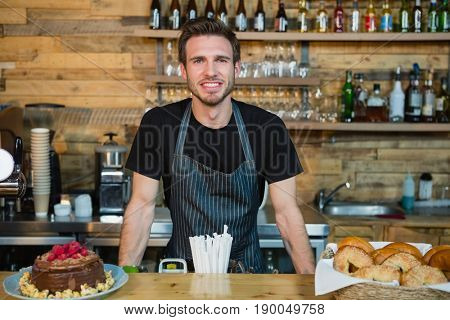 Portrait of smiling waiter leaning at counter in café