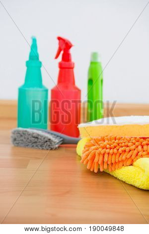 Close-up of chemical spray bottles and cleaning spone on hardwood flooring
