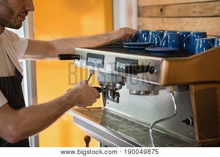 Waiter preparing coffee from coffee machine in café
