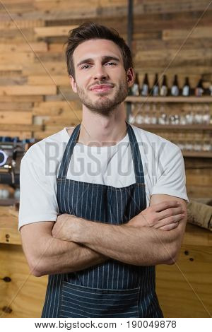 Portrait of smiling waiter standing with arms crossed in café