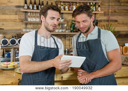 Waiters using digital tablet at counter in café