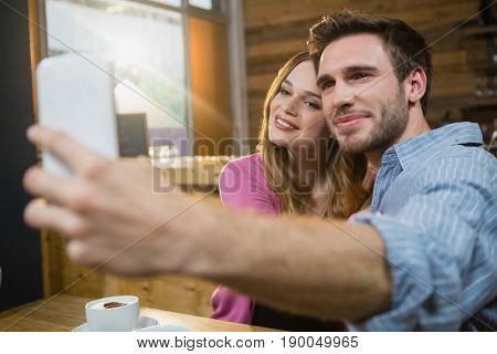 Young couple taking selfie on mobile phone while having coffee in café