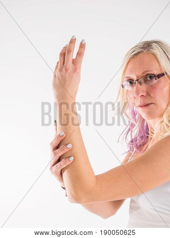 Female hand holding her forearm isolated on white background. Forearm pain, repetitive stress injury concept.
