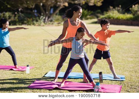 Young female instructor examining children praciting Virabhadrasana II pose at park