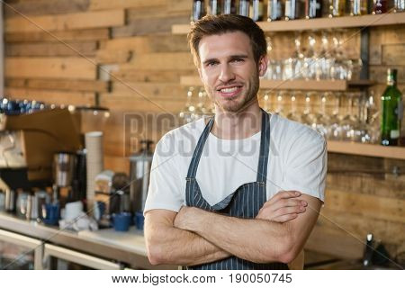 Portrait of smiling waiter standing with arms crossed at counter in café