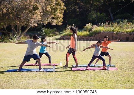 Young female trainer watching children praciticing Virabhadrasana II pose on mat