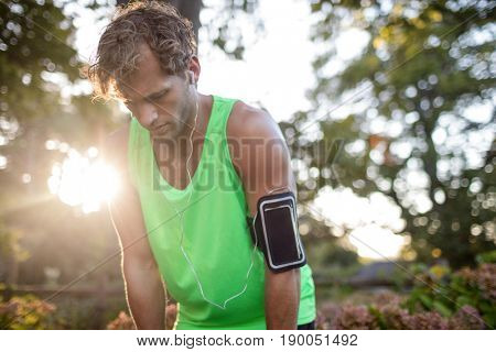 Tired man taking deep breath while jogging in park