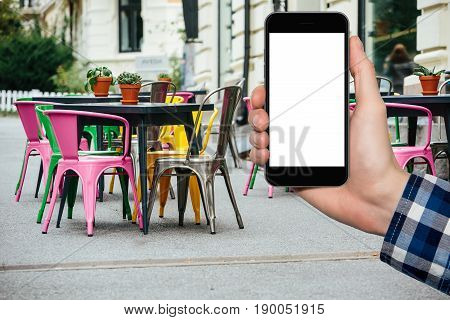 Man's hand with a smartphone on a background of a cafe in Europe.  White screen, you can insert your own image or text here.