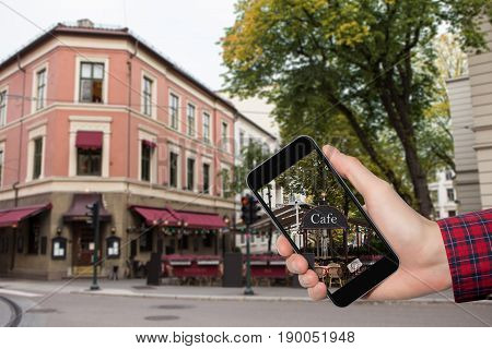 Man's hand with a phone on a background of city streets in Europe.