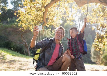 Father taking selfie with son holding stick in forest