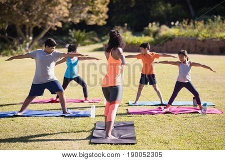 Female instructor teaching kids Virabhadrasana II on mat at park