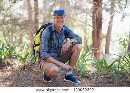 Portrait of happy mature male hiker kneeling on trail against trees