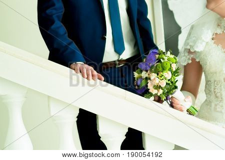the bride and groom stand near a white handrail indoors