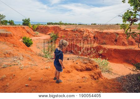 Young Boy In Red Canyon Near Mui Ne, Southern Vietnam. Traveling With Children Concept.