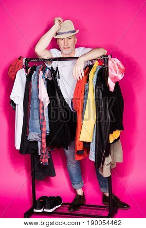 Senior Man Wearing Hat And Standing Behind Diferent Clothes On Hangers Isolated On Pink
