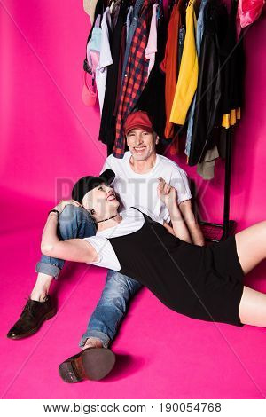 Cheerful Fashionable Senior Couple Resting Under Diferent Clothes On Hangers Isolated On Pink