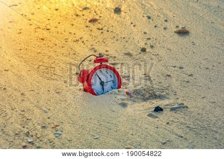 red clock in sand on the beach sun flare