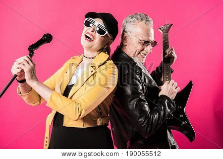 Cheerful stylish senior couple of rock and roll musicians performing isolated on pink