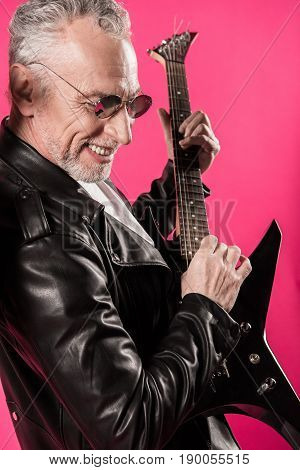 Joyful stylish senior man playing rock and roll music with electric guitar