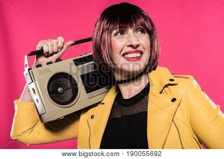 Smiling Stylish Senior Woman Holding Tape Recorder Isolated On Pink