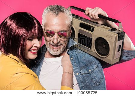 portrait of smiling woman hugging man with tape recorder isolated on pink