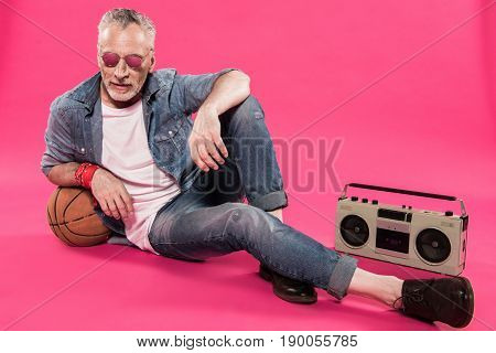 man sitting near tape recorder and basketball ball isolated on pink