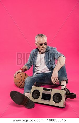 senior man sitting on floor with tape recorder and basketball ball isolated on pink