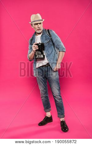 Stylish Senior Man Holding Photo Camera And Looking Away Isolated On Pink