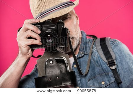 Obscured View Of Man Taking Picture On Retro Photo Camera Isolated On Pink
