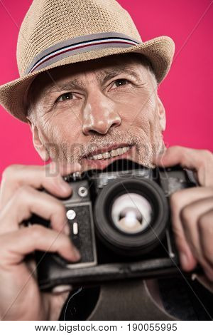 Portrait Of Smiling Man In Hat Holding Photo Camera And Looking Away Isolated On Pink