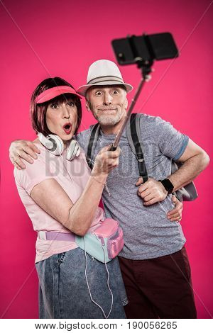 Portrait Of Grimace Senior Couple Taking Selfie On Monopod Isolated On Pink