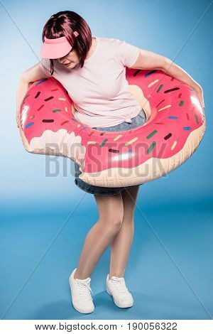 Stylish Woman Standing With Swimming Tube In Form Of Doughnut