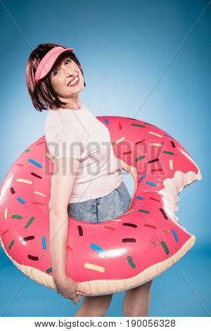 Smiling Stylish Woman With Swimming Tube In Form Of Doughnut Looking At Camera