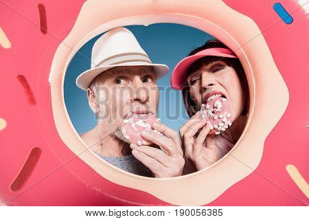 Portrait Of Elderly Couple Eating Sweet Doughnuts Into Swimming Tube