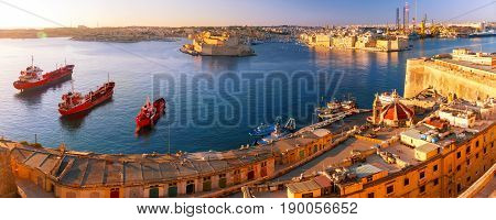 Panoramic skyline view of ancient defences of Valletta and the Grand Harbor with ships and Three cities, three fortified cities of Birgu, Senglea and Cospicua, at dawn. Malta.
