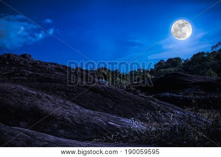 Landscape of blue sky with cloud and beautiful full moon over tranquil nature background. Dark tone. Outdoor at nighttime.
