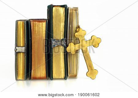 Religious items: old golden cross leant against Holy books with golden pages. White background