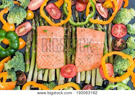 Raw Uncooked Salmon And Vegetables On Baking Tray