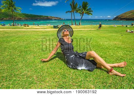 Woman relaxing in Hanauma Bay Nature Preserve, Oahu, Hawaii, USA. Smiling female in black beachwear, floppy hat, sunglasses enjoying on tropical destination during summer vacation on hawaiian beach.